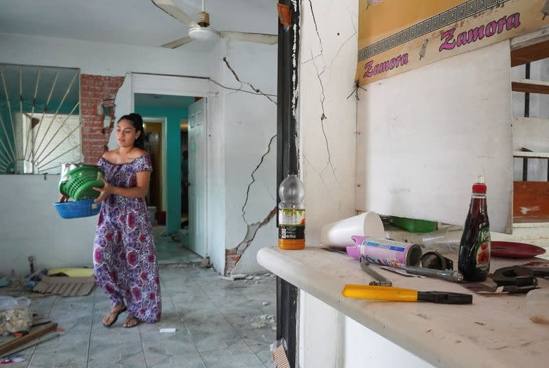 A woman carries kitchen utensils at her home damaged by a quake in Huatulco