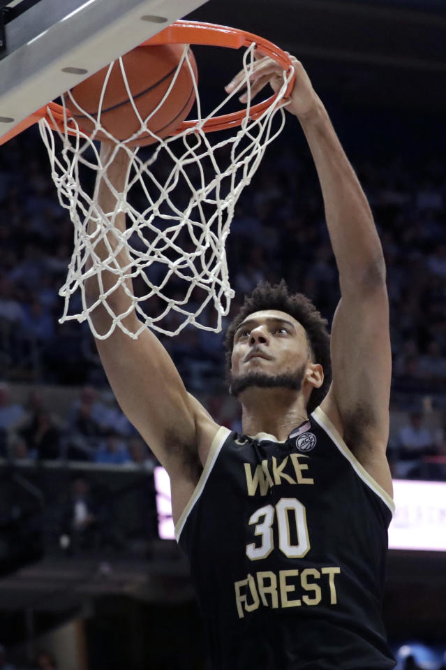 Wake Forest's Olivier Sarr (30) dunks against North Carolina during the second half of an NCAA college basketball game in Chapel Hill, N.C., Tuesday, March 3, 2020. (AP Photo/Chris Seward)