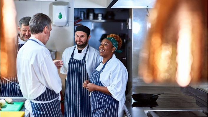 Colleagues working and talking in restaurant kitchen.
