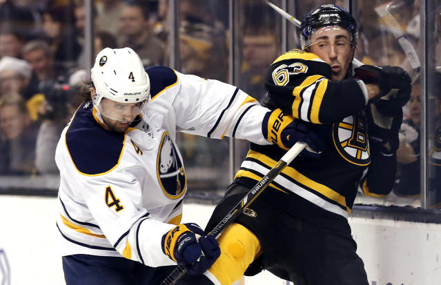 Buffalo Sabres' Jamie McBain (4) checks Boston Bruins' Brad Marchand into the boards during the second period of an NHL hockey game in Boston, Saturday, Dec. 21, 2013. (AP Photo/Winslow Townson)