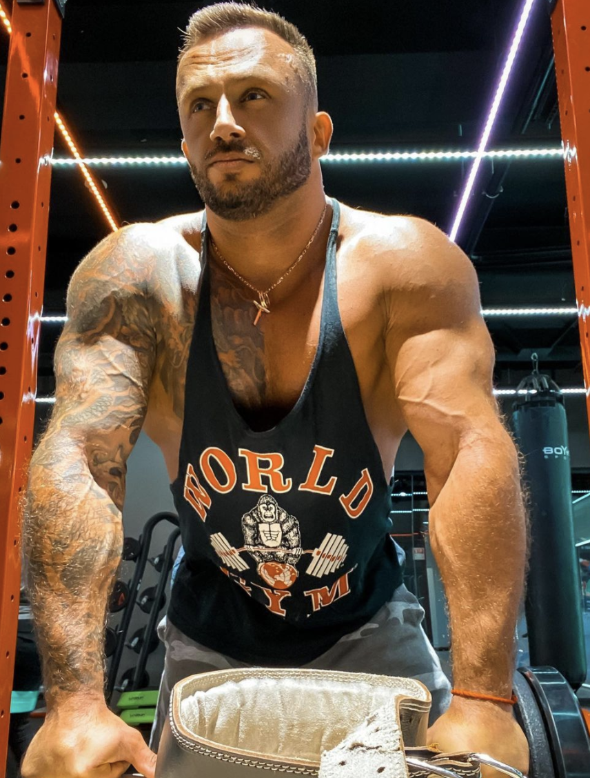 The 33-year-old fitness influencer is seen flexing in a gym.