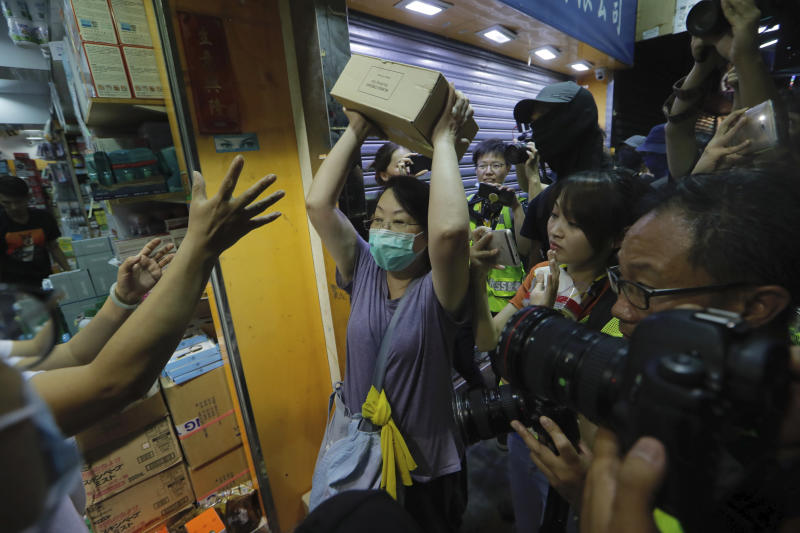 A protester throws a box of goods at a store that sells to mainland customers,  in Hong Kong,  Saturday, July 13, 2019. Several thousand people marched in Hong Kong on Saturday against traders from mainland China in what is fast becoming a summer of unrest in the semi-autonomous Chinese territory. (AP Photo/Kin Cheung)