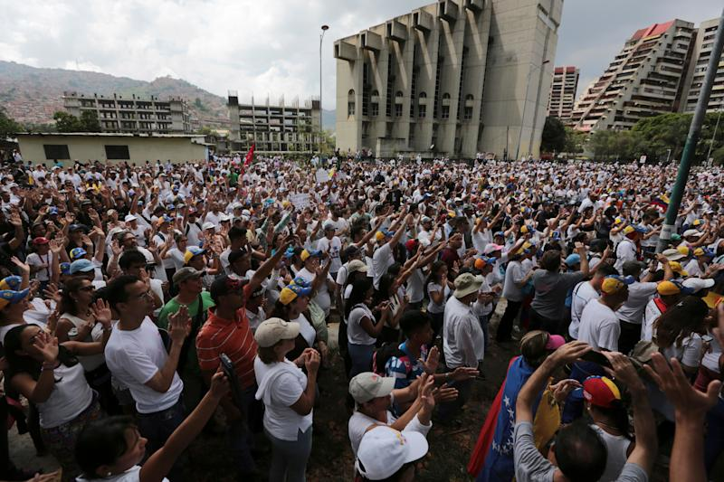 People gather for a silent protest outside the Venezuelan Episcopal Conference in homage to the at least 20 people killed in unrest. - Copyright 2017 The Associated Press. All rights reserved.