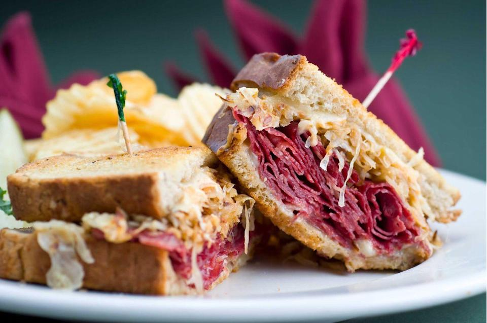 "<p><strong>Reuben Sandwich</strong></p><p>While it may not have been invented in Michigan, no one does Reuben Sandwiches like the delis in Detroit -- especially <a href=""https://www.zingermansdeli.com/"" rel=""nofollow noopener"" target=""_blank"" data-ylk=""slk:Zingerman's Deli"" class=""link rapid-noclick-resp"">Zingerman's Deli</a>. Thinly sliced corned beef and Swiss cheese, piled high only buttery rye bread, finished off with sauerkraut and Russian dressing. You can't go wrong grilled or hot-pressed. </p>"