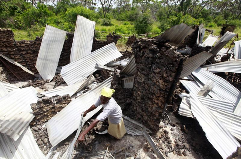 A resident rummages through the ruins of her building burnt down after gunmen attacked Hindi village, near Lamu