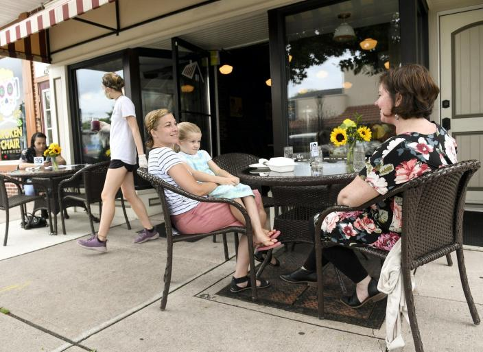 """<span class=""""caption"""">Patrons eat outside at a small cafe in West Reading, Pennsylvania, as the community begins to reopen.</span> <span class=""""attribution""""><a class=""""link rapid-noclick-resp"""" href=""""https://www.gettyimages.com/detail/news-photo/bambi-good-and-her-daughter-alaina-of-reinholds-talk-with-news-photo/1249265204"""" rel=""""nofollow noopener"""" target=""""_blank"""" data-ylk=""""slk:Ben Hasty/MediaNews Group/Reading Eagle via Getty Images"""">Ben Hasty/MediaNews Group/Reading Eagle via Getty Images</a></span>"""