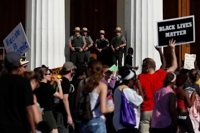 <p>Members of National Park Service watch as protesters pass the Old Courthouse after the not guilty verdict was announced in the murder trial of Jason Stockley, a former St. Louis police officer, charged with the 2011 shooting of Anthony Lamar Smith, in St. Louis, Mo., Sept. 15, 2017. (Photo: Whitney Curtis/Reuters) </p>