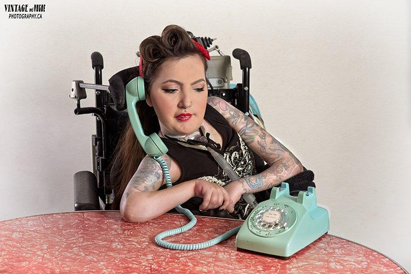 Crystal in retro pin-up attire using a teal vintage phone.