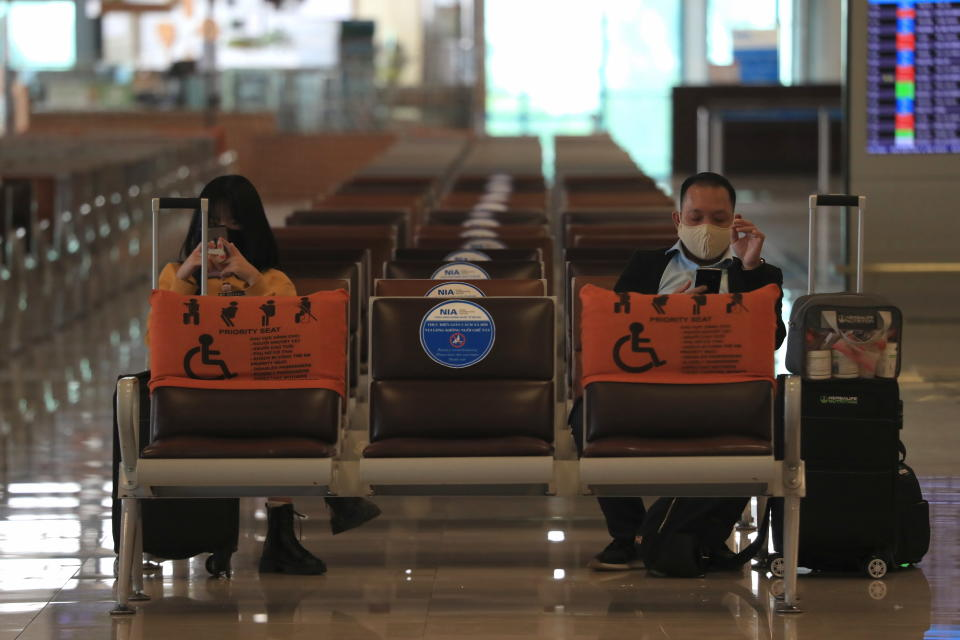 People wearing face masks wait for boarding at the Noi Bai airport in Hanoi, Vietnam, Friday, Feb.12, 2020. Fresh COVID-19 outbreak in Vietnam has slowed down business and travel during the popular lunar new year festival. (AP Photo/Hau Dinh)