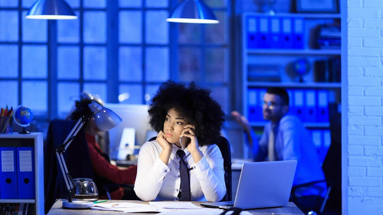 African woman working late in modern workplace.