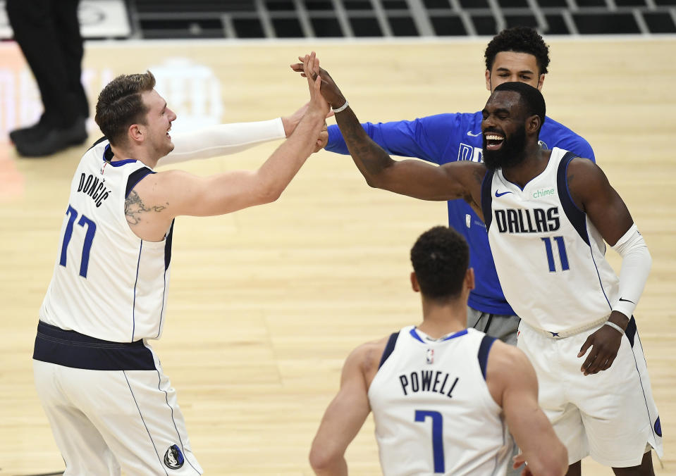 Luka Doncic of the Dallas Mavericks is congratulated by Tim Hardaway Jr.