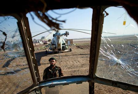 A soldier of the Afghan National Army (ANA) is seen through the cockpit of a derelict Russian helicopter as he guards Kunduz airport December 10, 2011. REUTERS/Thomas Peter