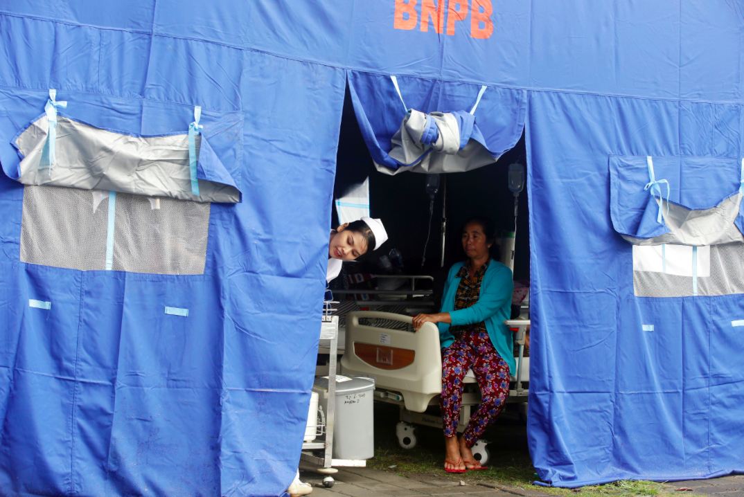 <p>A nurse looks out of a tent where patients were evacuated from a hospital in Bali (AP) </p>