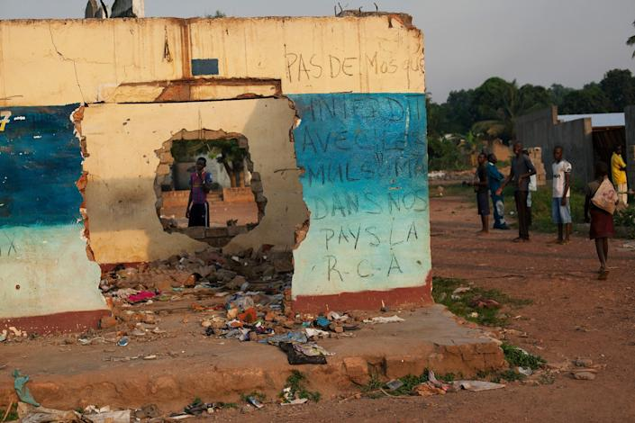 Men stand around a damaged shop that has been scrawled with graffiti reading 'No mosques, banned along with Muslims in our country, C.A.R.,' in the Fouh neighborhood of Bangui, Central African Republic, Monday, Dec. 23, 2013. The mosque that stood behind the shop was also destroyed in sectarian violence earlier in the month. Tension remained high in Bangui Monday as several Muslims were lynched in different parts of town and at least two Christians were injured when Chadian soldiers drove through a protest, firing off several rounds. (AP Photo/Rebecca Blackwell)