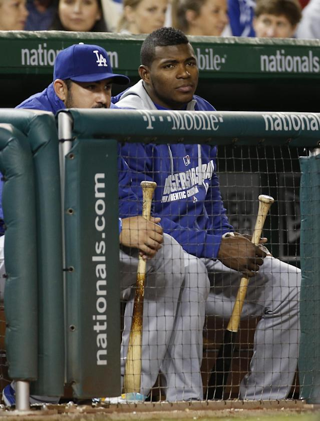 Los Angeles Dodgers right fielder Yasiel Puig, right, watches from the dugout during a baseball game against the Washington Nationals at Nationals Park, Tuesday, May 6, 2014, in Washington. The Dodgers won 8-3. (AP Photo/Alex Brandon)