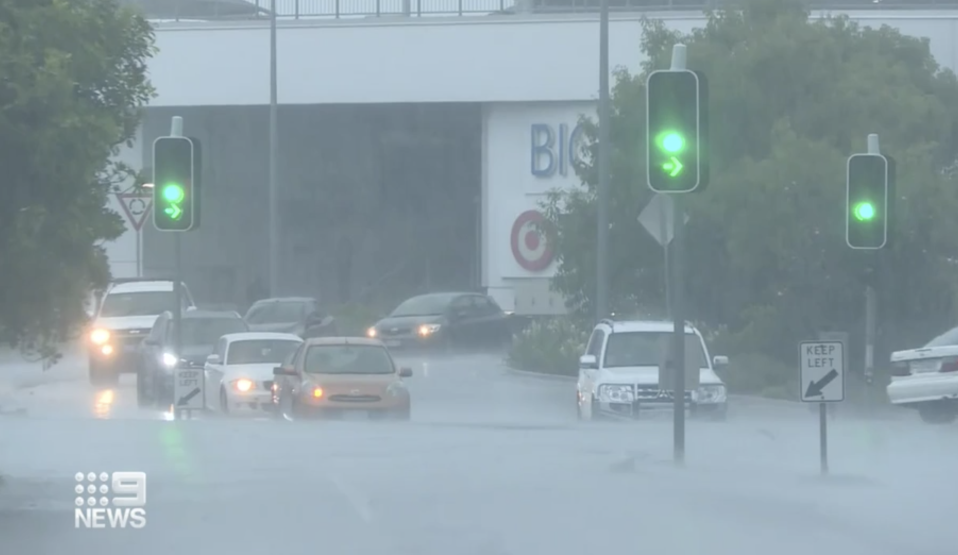 Cars drive through flooded roads in North Queensland.