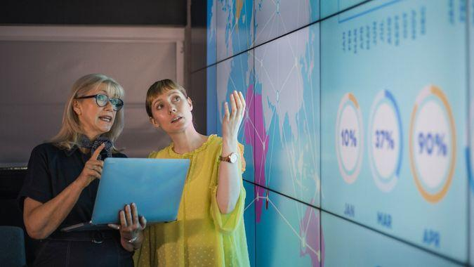 An experienced woman mentors a female colleague, the mature woman is holding a laptop as they debate data from an interactive display; they are both wearing smart casual clothing.