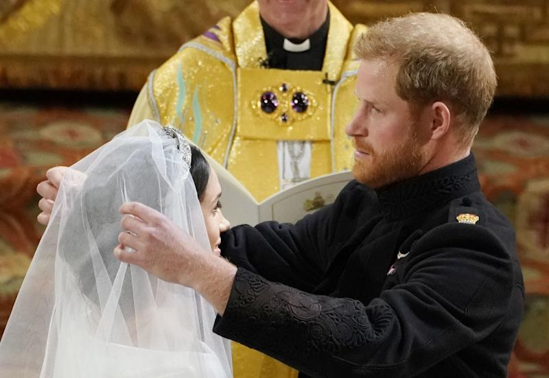Prince Harry lifts the veil of Meghan Markle during their wedding ceremony in St George's Chapel at Windsor Castle on May 19, 2018 in Windsor, England.