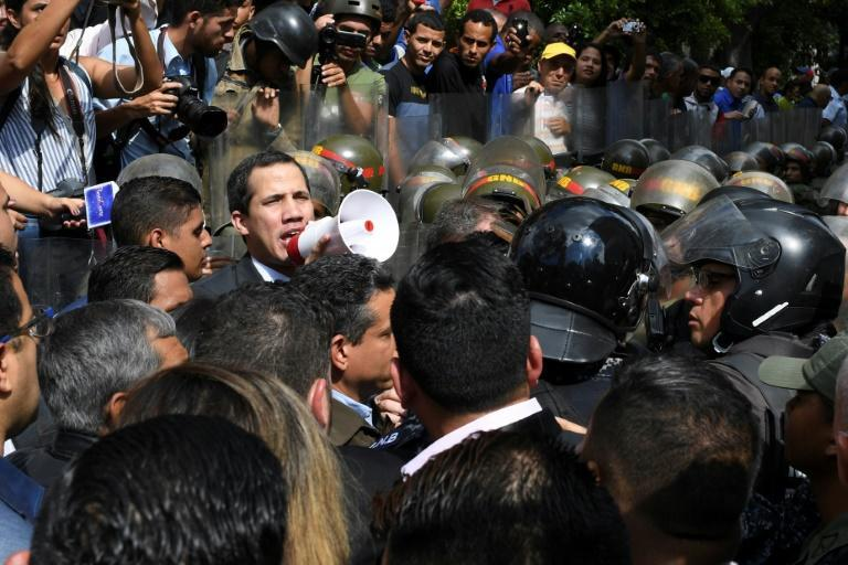 Venezuelan opposition leader and self-proclaimed acting president Juan Guaido speaks on a loudspeaker as helmeted security forces try to block his entry to the National Assembly
