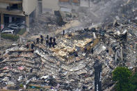 FILE - In this June 25, 2021, file photo, rescue workers search in the rubble at the Champlain Towers South Condo in Surfside, Fla. Search and rescue teams from Miami-Dade have been described as among the best and most experienced in the world. (AP Photo/Gerald Herbert, File)