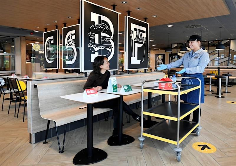 A customer receives her order inside a prototype location of fast food giant McDonald's for restaurants which respect the 1.5m social distancing measure, amid the coronavirus disease (COVID-19) outbreak, in Arnhem, Netherlands, May 1, 2020. REUTERS/Piroschka van de Wouw