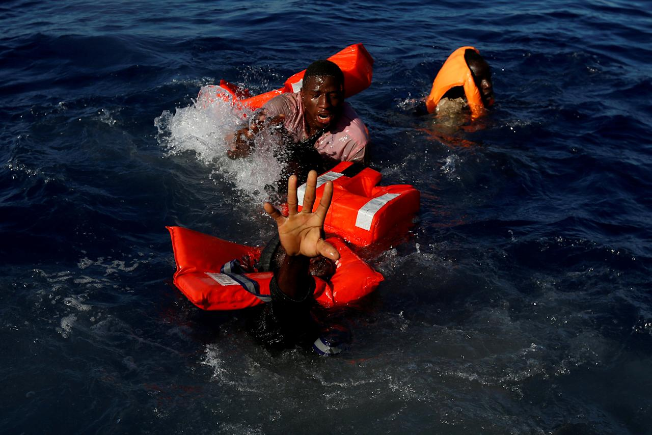"Migrants try to stay afloat after falling off their rubber dinghy during a rescue operation by the Malta-based NGO Migrant Offshore Aid Station (MOAS) ship in the central Mediterranean in international waters some 15 nautical miles off the coast of Zawiya in Libya, April 14, 2017. All 134 sub-Saharan migrants survived and were rescued by MOAS. Darrin Zammit Lupi: ""I spent five weeks with the Migrant Offshore Aid Station (MOAS) on their ship, Phoenix, covering search and rescue operations in the Mediterranean. At the start of the Easter weekend we were on a routine rescue around 15 nautical miles off the Libyan coast. I was on the MOAS fast rubber boat with crew members handing out life jackets to a group of 134 Sub-Saharan migrants on a flimsy dinghy before we would transfer them to the Phoenix. I had one camera up to my eye to shoot some wide angle frames. Suddenly, one migrant balancing on the rim of a dinghy slipped sideways and like dominos several of his colleagues lost their balance and fell into the sea. I captured the whole sequence by keeping my finger on the shutter button. It was chaos. I kept shooting as the rescuers leapt into action, helping several of the migrants pull themselves onto our boat. I was grabbing hold of people with one hand and shooting with the other. Then, through my viewfinder, a few metres away, I noticed one man struggling more than the others, stretching out his arm towards us. I screamed to alert our specialist rescue swimmer that one man was going under. He reacted instantly, jumped in, and pulled the man to safety. Afterwards, I did a lot of soul searching. Should I have put down my cameras altogether and just grabbed hold of whoever I could? That evening I discussed it with the rescuers, who felt I'd done the right thing. Their job was to rescue lives. Mine was to document the harsh reality of what's happening. Everyone survived that day."" REUTERS/Darrin Zammit Lupi/File photo  SEARCH ""POY STORY"" FOR THIS STORY."