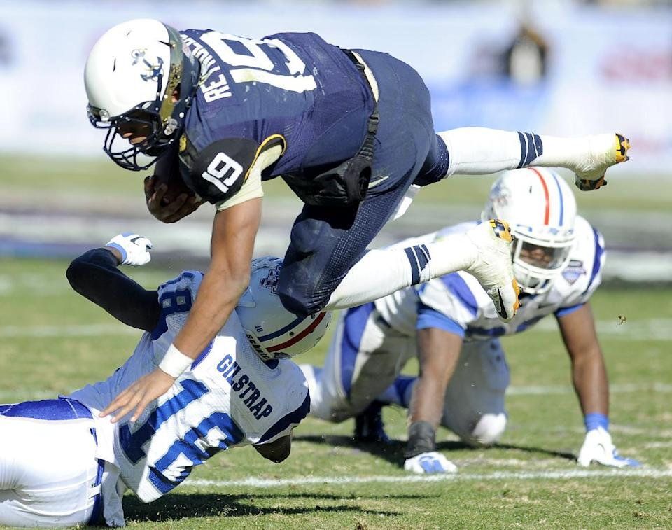 Navy Midshipmen quarterback Keenan Reynolds (19) is tripped up by Middle Tennessee Blue Raiders cornerback Kenneth Gilstrap (18) in the first half of the Armed Forces Bowl NCAA college football game, Monday, Dec. 30, 2013, in Fort Worth. (AP Photo/Matt Strasen)
