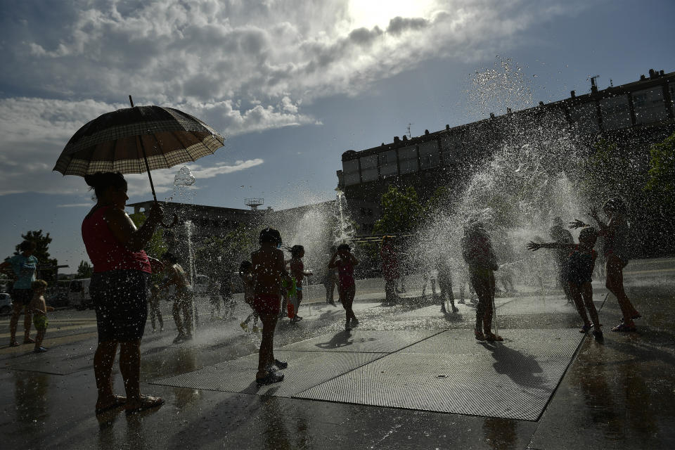 People cool off in a fountain in Pamplona, northern Spain (AP Photo/Alvaro Barrientos)