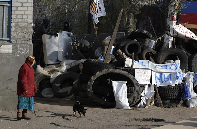 """A woman walks her dog along a barricade in downtown Slovyansk , eastern Ukraine, Wednesday, April 16, 2014. The city of Slovyansk has come under the increasing control of the pro-Russian gunmen who seized it last weekend. The Slogans read: """"No to Fascism, Yes to referendum, Soldier do not shoot."""" (AP Photo/Sergei Grits)"""
