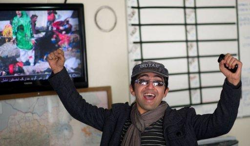 Massoud Hossaini reacts as he sees his photograph reproduced on Afghan television at the AFP office in Kabul