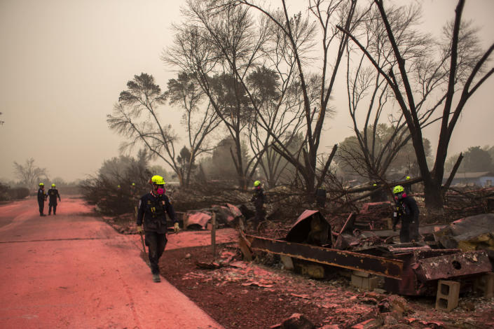 Members of a search and rescue team walk along a sidewalk stained by fire retardant in Talent, Ore., after the Almeda fire passed, on Sept. 13, 2020. (Alisha Jucevic/The New York Times)