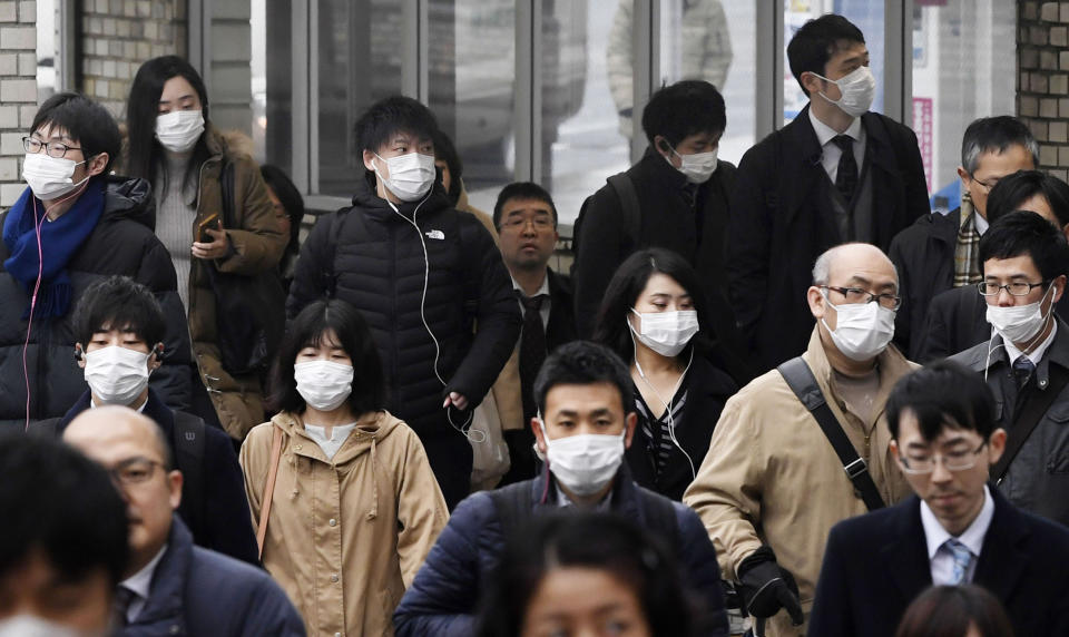 People wearing face masks walk on a street in Nara, western Japan, Wednesday, Jan. 29, 2020. Japan's health officials on Tuesday said that it has confirmed what could be the first human-to-human infection in the country. The first suspected person-to-person infection involves a male patient in his 60s from Nara, who has not traveled to Wuhan. The man, however, is a tour bus driver who served two groups of Chinese tourists from Wuhan from Jan. 8-16. (Nobuki Ito/Kyodo News via AP)