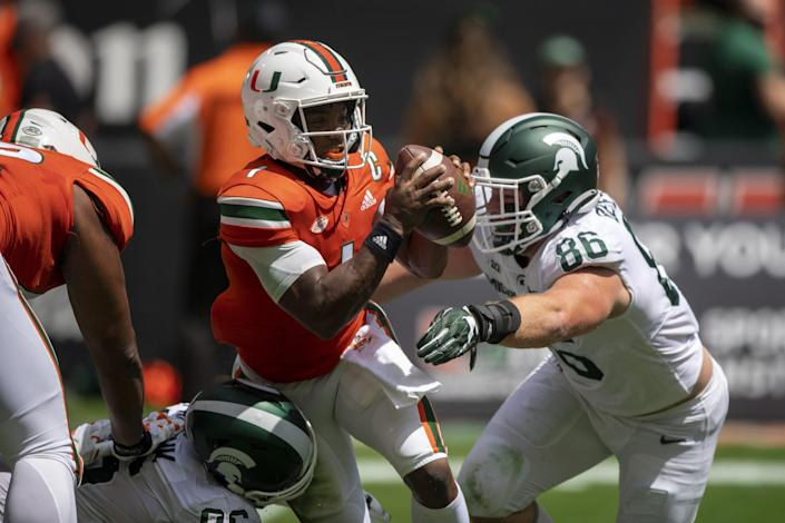 Miami quarterback D'Eriq King (1) runs with the ball under pressure from Michigan State defensive end Drew Beesley (86) during an NCAA football game on Saturday, Sept 18, 2021 in Miami Gardens, Fla. (AP Photo/Doug Murray)