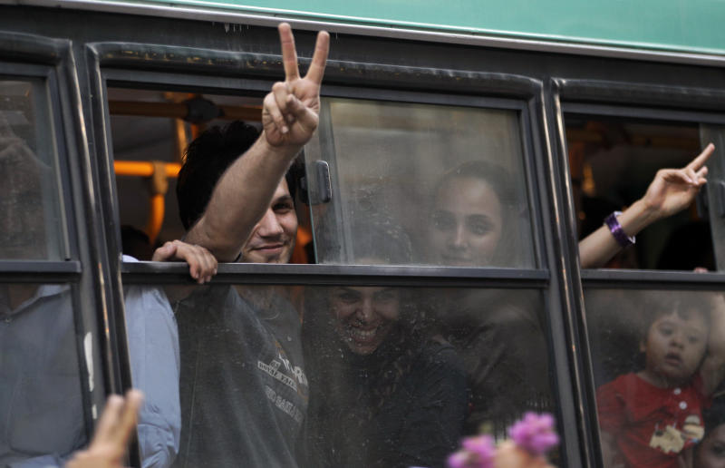 Passengers in a public bus flash victory signs in a reaction of supporters of the Iranian presidential candidate Hasan Rowhani, as they attend a celebration gathering, in Tehran, Iran, Saturday, June 15, 2013. Moderate cleric Hasan Rowhani was declared the winner of Iran's presidential vote on Saturday after gaining support among many reform-minded Iranians looking to claw back a bit of ground after years of crackdowns. (AP Photo/Vahid Salemi)