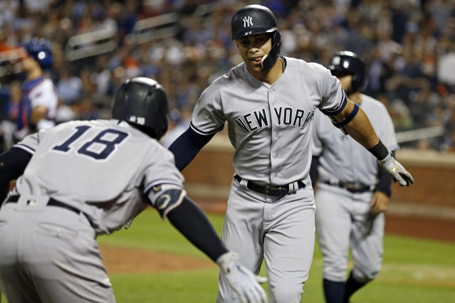New York Yankees' Giancarlo Stanton, front right, celebrates a solo home run with teammate Didi Gregorius (18) during the ninth inning of a baseball game against the New York Mets, Friday, June 8, 2018, in New York. (AP Photo/Adam Hunger)
