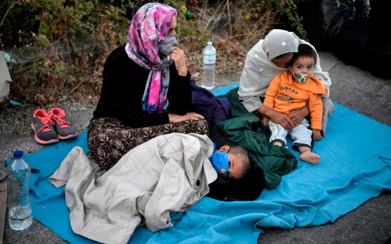 A refugee family sitting in the road after Moria camp was destroyed by fire - AFP