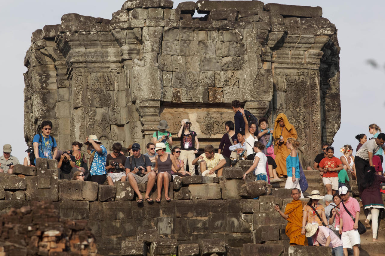 In this photo taken on May 11, 2011, western tourist and others gather on the top of the 10th century temple Bakheng in the Angkor Wat complex near Siem Reap, Cambodia, to view the setting sun. A traffic jam of up to 3,000 tourists surges up a steep hillside, trampling over vulnerable stonework and quaffing beer at a sacred hilltop that provides spectacular sunset views of the massive beehive-like towers rising from the main temple in this ancient city: Angkor Wat. (AP Photo/David Longstreath)