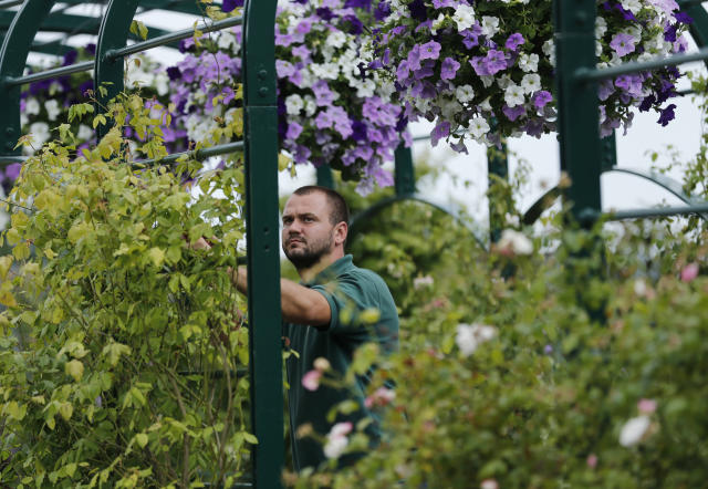 FILE - In this Sunday, June 22, 2014, file photo, a groundsman prepares a flower display the day before the tennis tournament starts at the All England Lawn Tennis Championships in Wimbledon, London. (AP Photo/Ben Curtis, File)
