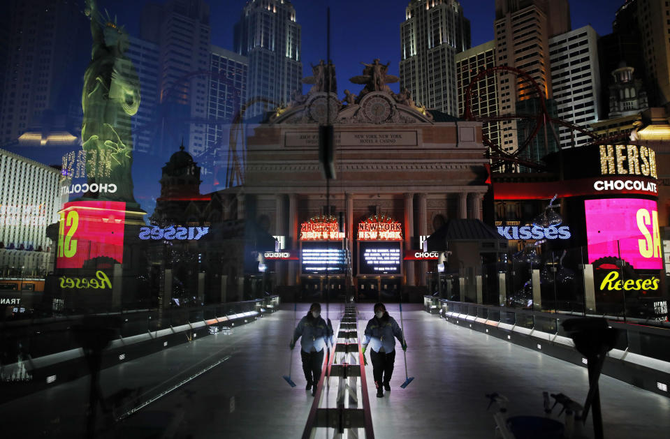 In this April 18, 2020, photo, a lone worker wearing a mask cleans a pedestrian walkway devoid of the usual crowds as casinos and other business are shuttered due to the coronavirus outbreak in Las Vegas. Nevada's governor closed the glitzy casinos and nightlife attractions in mid-March, leaving much of the famous gambling mecca empty, barricaded and abandoned. (AP Photo/John Locher)