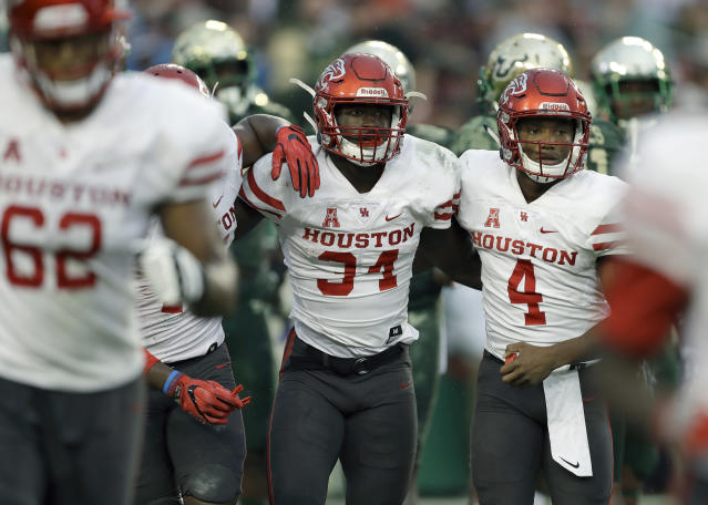 """Houston running back Mulbah Car (34) celebrates with quarterback <a class=""""link rapid-noclick-resp"""" href=""""/ncaaf/players/266770/"""" data-ylk=""""slk:D'Eriq King"""">D'Eriq King</a> (4) after scoring on a 4-yard touchdown run against South Florida during the second half of an NCAA college football game, Saturday, Oct. 28, 2017, in Tampa, Fla. Houston upset South Florida 28-24. (AP Photo/Chris O'Meara)"""
