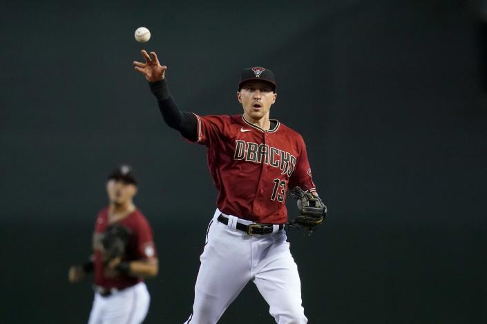 Arizona Diamondbacks shortstop Nick Ahmed (13) throws to first base to get out Chicago Cubs' Anthony Rizzo as Diamondbacks second baseman Josh Rojas looks on during the first inning of a baseball game, Sunday, July 18, 2021, in Phoenix. (AP Photo/Ross D. Franklin)