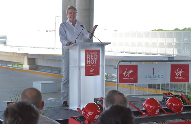 """Wes Edens, Chairman of Virgin Trains USA, speaks in the early part of the groundbreaking ceremony for Virgin Trains USA on Monday, June 24, 2019, at the Orlando International Airport. """"There's probably no better place in America that it [the train] could exist than where we're standing today,"""" Edens said."""