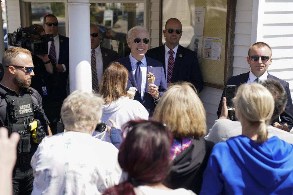 President Joe Biden talks with people as he holds an ice cream cone at Honey Hut Ice Cream, Thursday, May 27, 2021, in Cleveland. (AP Photo/Evan Vucci)