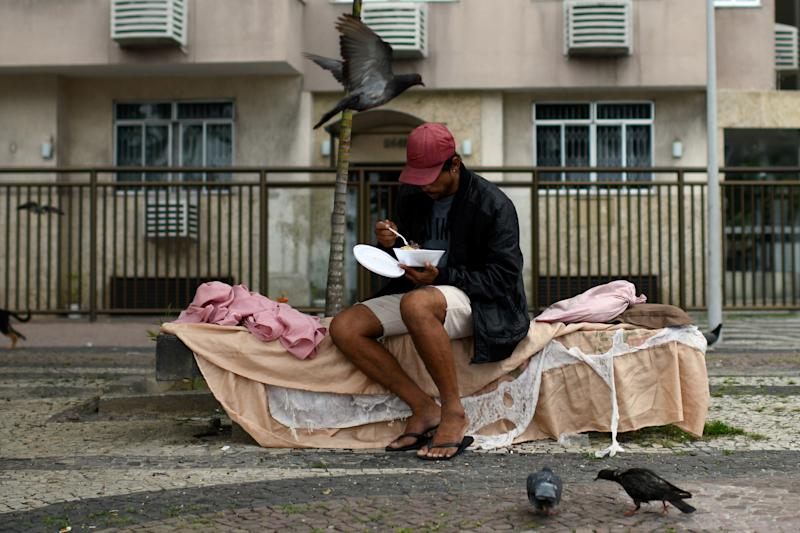 A homeless person eats after receiving food from a group of residents of the Chapeu Mangueira slum, during the coronavirus disease (COVID-19) outbreak, at Copacabana neighborhood in Rio de Janeiro, Brazil, April 11, 2020. REUTERS/Lucas Landau TPX IMAGES OF THE DAY