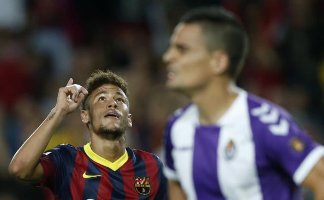 Barcelona's Neymar (L) celebrates a goal as Real Valladolid's Carlos Pena reacts during their Spanish First division soccer league match at Camp Nou stadium in Barcelona, October 5, 2013. REUTERS/Albert Gea (SPAIN - Tags: SPORT SOCCER)