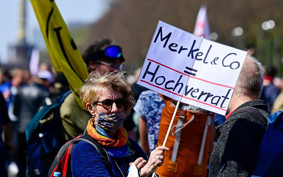 """An anti Covid-19 protestor holds a placard reading, """" Merkel & CO = High treason) while taking part in a demonstration in Berlin - TOBIAS SCHWARZ / AFP"""