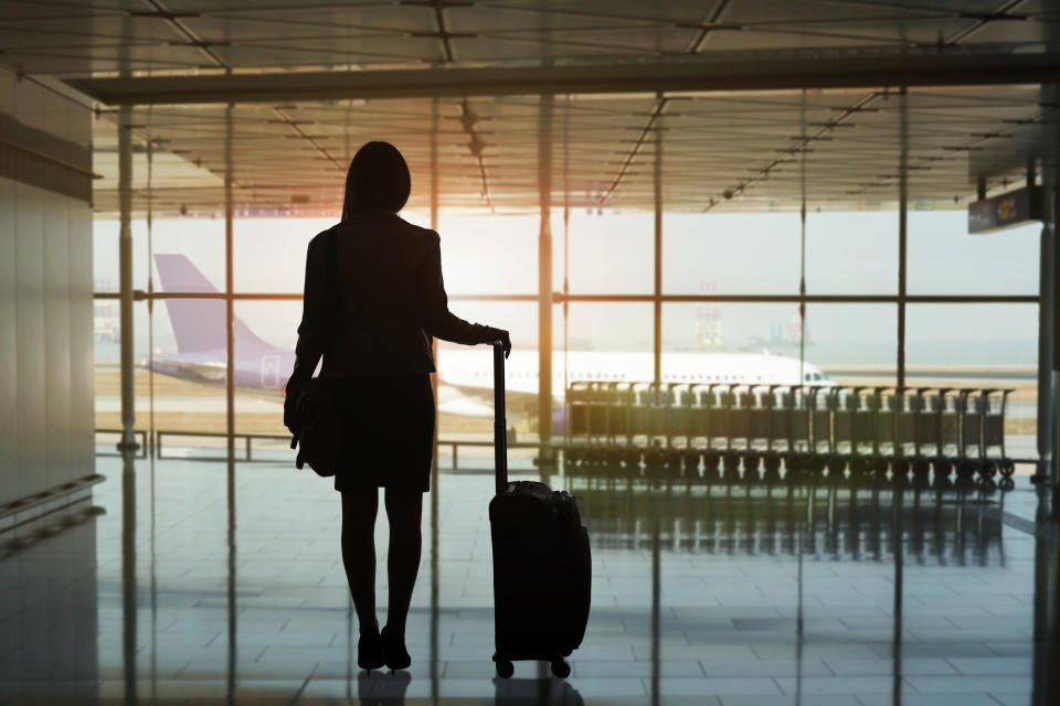 Silhouette of a woman traveller waiting for her flight at Hong Kong International Airport.