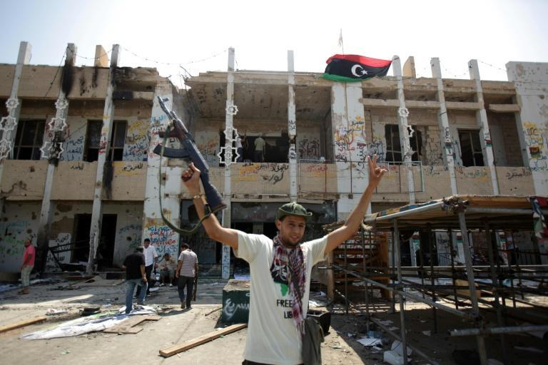 A Libyan rebel fighter celebrates the seizure of Bab al-Aziziya in August 2011 after NATO bombardment destroyed much of the sprawling compound