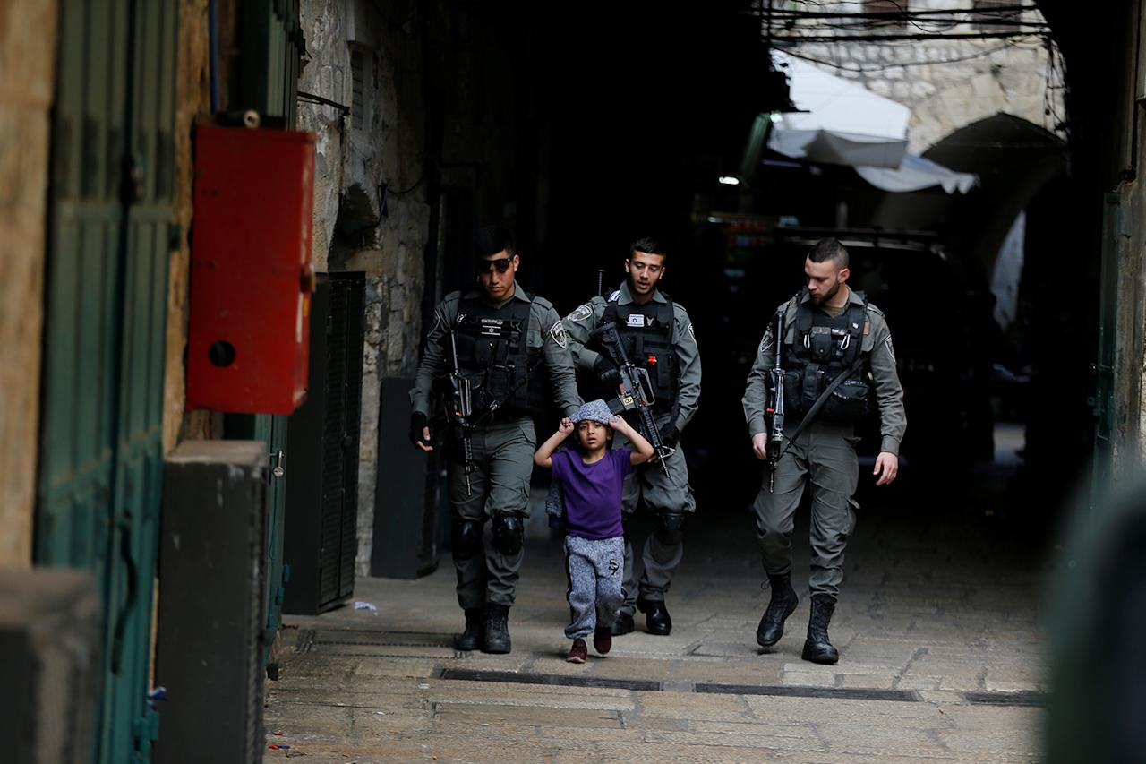 <p>Israeli border policemen escort a boy away from a blocked alley after a stabbing attack inside the old city of Jerusalem according to Israeli police, April 1, 2017. (Photo: Ammar Awad/Reuters) </p>