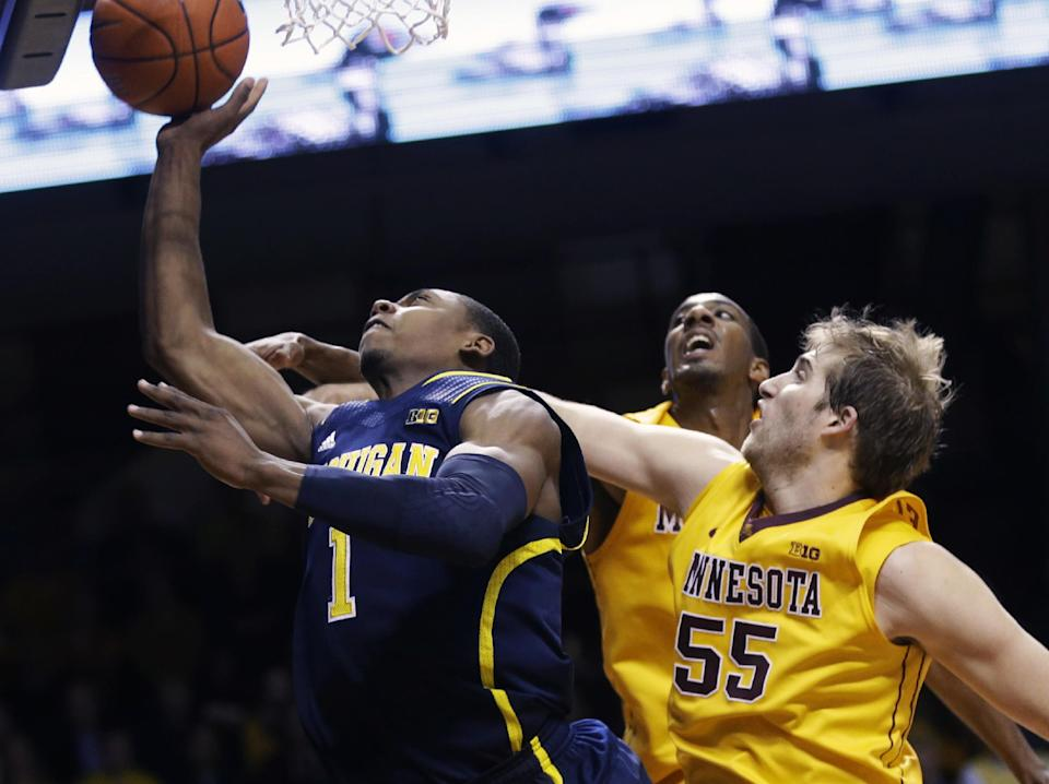 Minnesota's Elliott Eliason, right, tries to break up a shot attempt by Michigan's Glenn Robinson III during the first half of an NCAA college basketball game Thursday, Jan. 2, 2014, in Minneapolis. (AP Photo/Jim Mone)